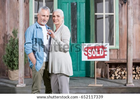 happy senior couple holding keys of their new house and standing on porch #652117339