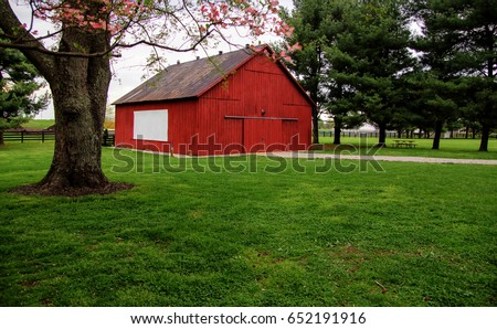 Red Kentucky Barn. Rural red barn with picket fence in the background. This structure is located in a Kentucky State Park and not private property. #652191916