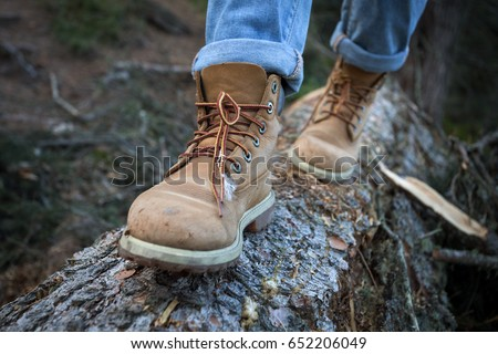 hiking boots close-up. girl tourist steps on a log #652206049