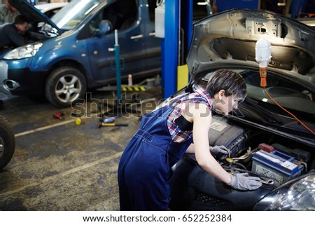 Young female in uniform checking car engine #652252384