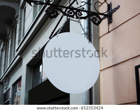 Signboard side view of empty white mock up signage with old city wall background display exterior. Medieval, middle age style with artistic metal blacksmithing decoration #652353424