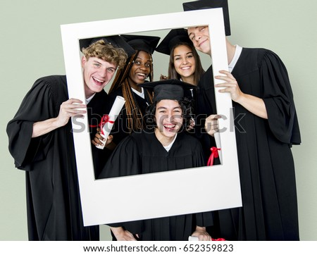 Diverse Students wearing Cap and Gown Holding Photo Frame Studio Portrait #652359823