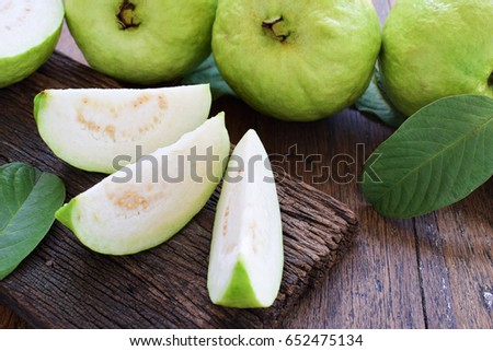Three slices of green guava fruit with leaf on rough old wood and wooden table. #652475134