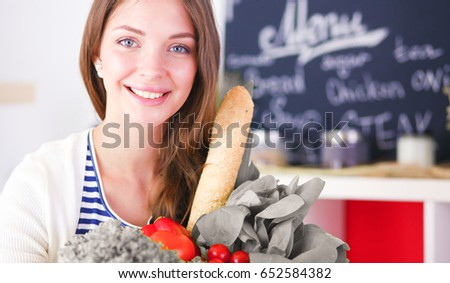 Young woman holding grocery shopping bag with vegetables #652584382
