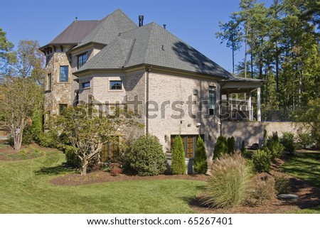 Side view of upscale house in wooded setting #65267401