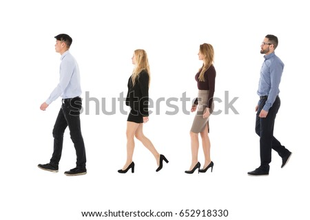 Male And Female College Students Walking In Row Against White Background #652918330