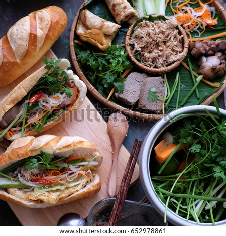 Famous Vietnamese food is banh mi thit, popular street food from bread stuffed with raw material: pork, ham, pate, egg and fresh herbs as scallions, coriander, carrot, cucumber, chilli. Royalty-Free Stock Photo #652978861