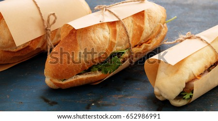 Famous Vietnamese food is banh mi thit, popular street food from bread stuffed with raw material: pork, ham, pate, egg and fresh herbs as scallions, coriander, carrot, cucumber, chilli. Royalty-Free Stock Photo #652986991