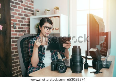 lovely young business photo company worker sitting in office drinking hot coffee and using mobile digital tablet computer checking photographer picture for editing.