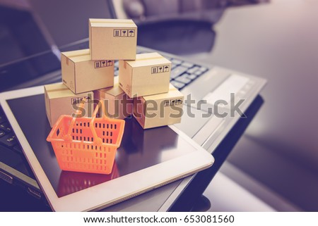 Mini orange shopping basket on a smart device and a laptop with boxes. Concept of shopping that client can buy or purchase goods or products from websites worldwide via internet by just a few clicks. #653081560