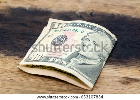 A picture of a folded ten USA dollar note on a wooden background.  This image can be used to represent payment or money.