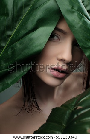Beauty portrait of a girl looking out from green leaves #653130340
