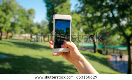 Woman taking photo on smartphone in the park