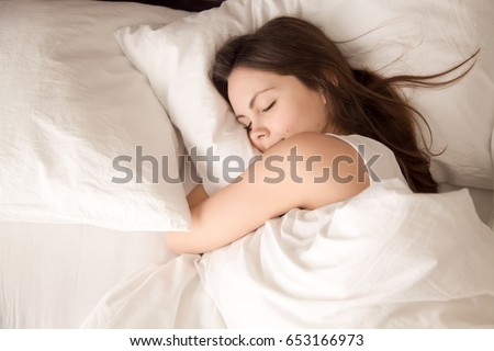 Top view of attractive young woman sleeping well in bed hugging soft white pillow. Teenage girl resting, good night sleep concept. Lady enjoys fresh soft bedding linen and mattress in bedroom  Royalty-Free Stock Photo #653166973
