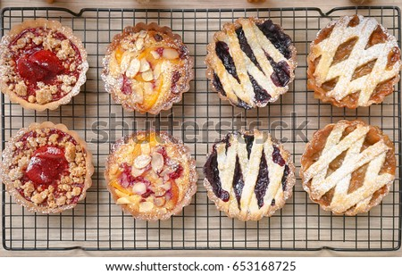 tart top view. from left to right : strawberry crumble tarts, peach raspberry almond tarts, blueberry tarts, apple rhubarb tarts #653168725