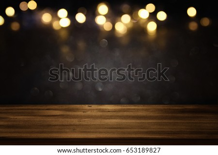 Empty table in front of black and gold glitter lights background. For product display montage