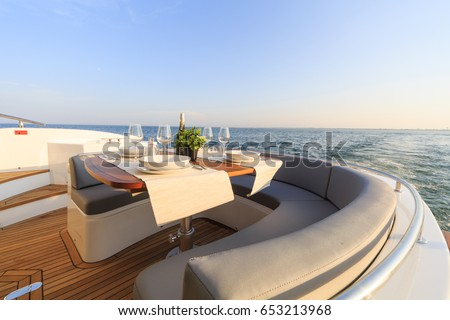 romantic lunch on motor yacht at sunset, Table setting at a luxury yacht. Royalty-Free Stock Photo #653213968