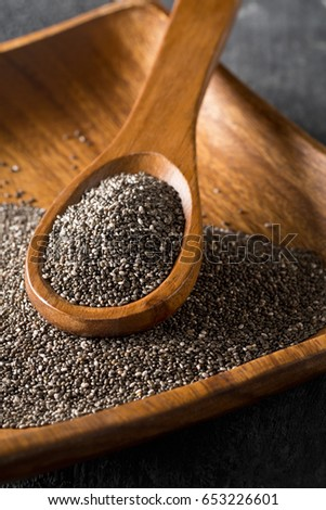 Raw unprocessed black chia seeds on wooden spoon on chia seed background #653226601