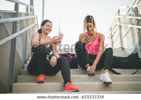 Two young female athletes listening to the music after workout #653235334