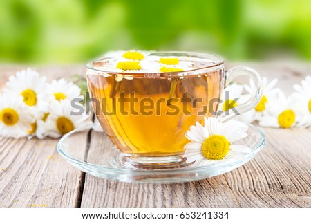 cup of chamomile tea and  chamomile flowers on wooden background #653241334