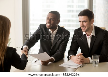 Two cheerful black and white recruiters welcoming female applicant on job interview, african and caucasian hr managers greeting candidate for vacant position, handshaking and good first impression Royalty-Free Stock Photo #653243296