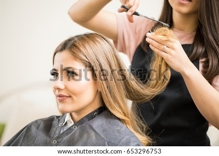 Portrait of a gorgeous young blonde getting her hair cut by a hairstylist at a beauty salon #653296753