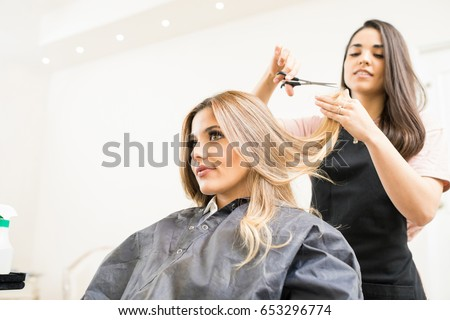 Pretty brunette working as a hairdresser and cutting hair tips of a female customer in a beauty salon #653296774