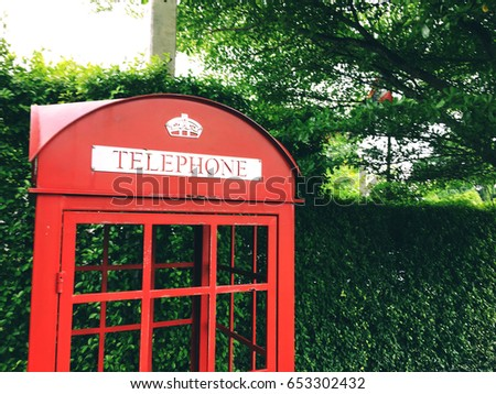 Red telephone box decorate in the English garden style #653302432