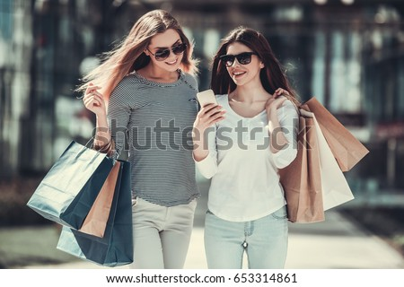 Beautiful girls in sun glasses are holding shopping bags, using a smart phone and smiling while standing outdoors #653314861