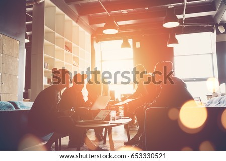 Silhouette of startup business team. Meeting on the couch. Big open space office. Five people. Intentional sun glare and lens flares Royalty-Free Stock Photo #653330521