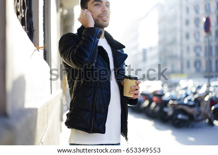 Smiling man having mobile conversation with friends on cellphone connected to 4G internet and carefully listening.Hipster guy strolling in the city with modern device and coffee cup at sunny evening #653349553