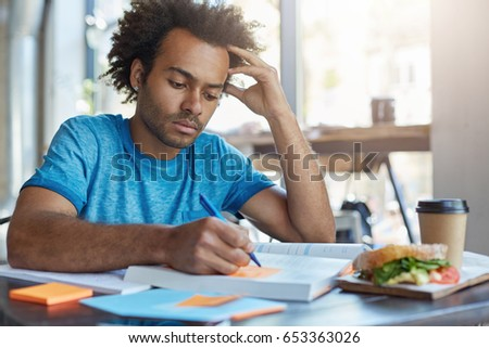 Handsome serious black European male student busy learning lessons during lunch at cafe, sitting at table with food and textbooks, making notes, writing down new words preparing for Spanish class Royalty-Free Stock Photo #653363026