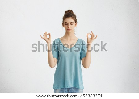 Yoga and meditation. Beautiful casually dressed young woman keeping eyes closed while meditating, feeling relaxed, calm and peaceful after hard working day at office, holding hands in mudra sign