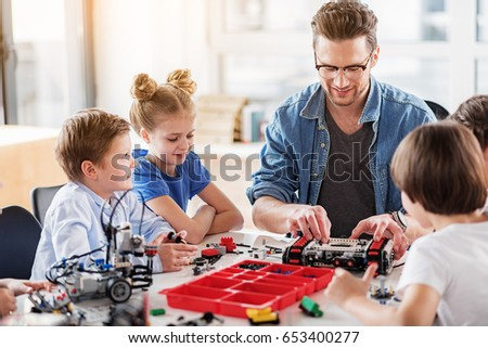 Cheerful smiling constructor checking technical toy #653400277