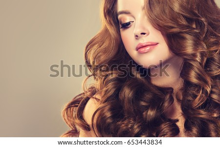 Brunette  girl with long  and   shiny wavy hair .  Beautiful  model woman ,  with curly hairstyle . #653443834