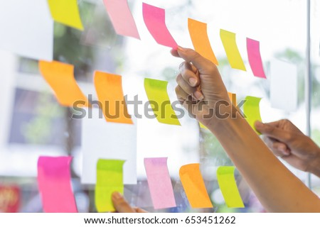 business people post it notes in glass wall at meeting room Royalty-Free Stock Photo #653451262