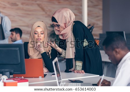 Two woman with hijab working on laptop in office. #653614003
