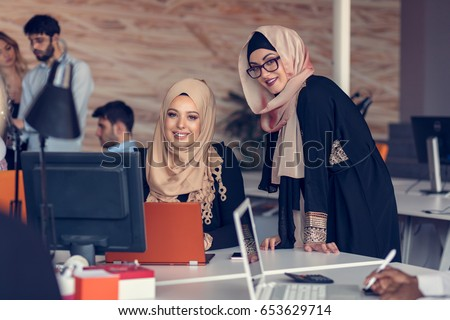 Two woman with hijab working on laptop in office. #653629714