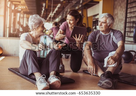 Senior couple in rehabilitation center. Personal trainer showing something on digital tablet. #653635330
