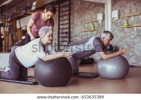 Senior people workout in rehabilitation center. Personal trainer helping senior people on Pilates ball. #653635384