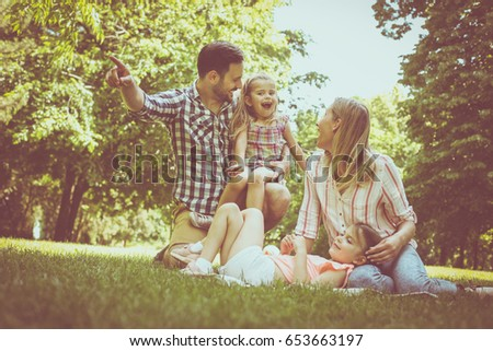 Happy family sitting on grass in the meadow together and enjoying in summer day. #653663197