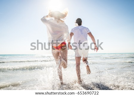Couple strolling at the beach and smiling - Young adults enjoying summer holidays on a tropical island #653690722