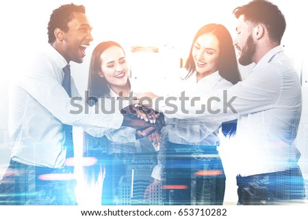 Members of a diverse business team are standing in a circle with their hands together teaming up. They are having fun and being successful. Toned image film effect #653710282