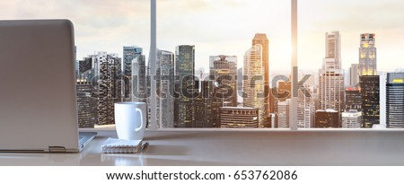 Laptop on table in office with panoramic sunset view of modern downtown skyscrapers at business district #653762086