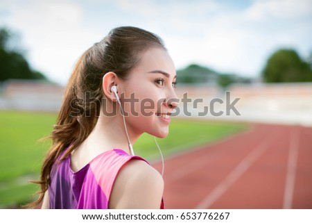 Fitness Asia woman with sport in-ear wireless headphones. Asian female athlete woman runner wearing earphones with wing tip design for sports activities. Portrait closeup.
