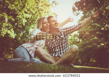 Happy couple in the park. Happy couple taking self-picture with phone.