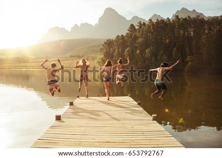 Group of young people jumping into the water from a jetty. Group of friends jumping from pier in the lake on a sunny day. #653792767