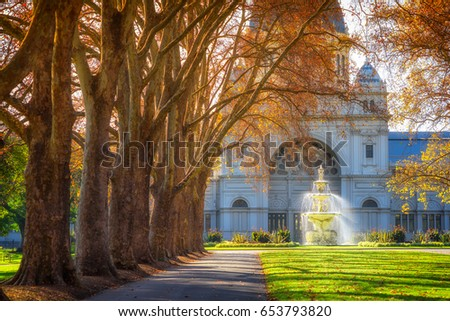 A row of trees leading to a fountain in front of the Royal Exhibition Building at Carlton Gardens in Melbourne, Australia. #653793820