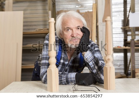 Serious furniture designer carefully polishes the chair frame, which he is busy manufacturing in his woodwork workshop, with shelves of wooden objects and patterns behind him #653854297