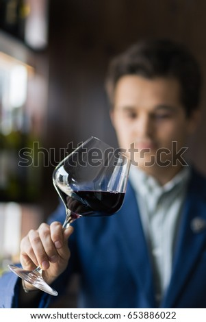 Focused young male sommelier in suite looking at red wine in glass over white background #653886022
